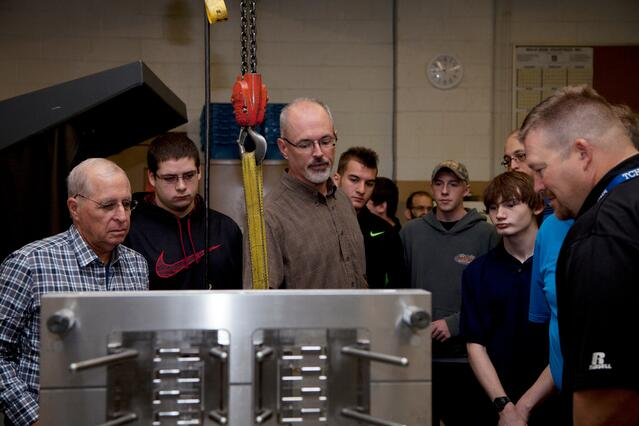 group of high school age boys and Rodon employees gather around a stainless steel injection mold